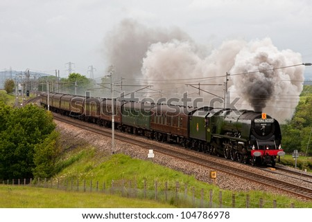 HACKTHORPE, ENGLAND - JUNE 9: Preserved steam locomotive 46233 Duchess of Sutherland heads the Royal Scot southbound through Hackthorpe, Cumbria on June 9, 2012, on the west coast mainline.