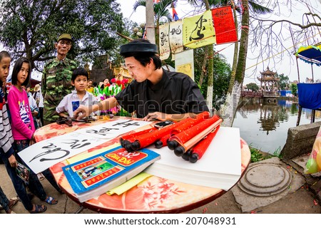 HAI HAU, NAMDINH, VIETNAM - APRIL 13, 2014 - An unidentified calligraphist writing calligraphy at a transitional festival . People enjoy  calligraphy at festivals as a cultural characteristic.