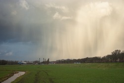 Hail and snow fall streaks of a wintry shower over the dutch landscape