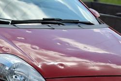 Hail damage at car, red colored car