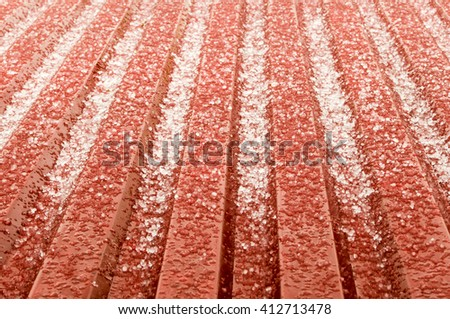 hail ice rain on a red corrugated tin roof variant. the hail corns have just smashed on the roof but instantly they start to melt and transform into water