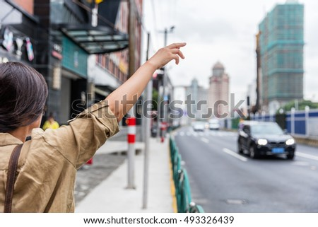 Hailing a rideshare black car on the road. Asian woman with hand up calling a taxi cab on Shanghai street, China using phone app technology for passenger to request a ride online.
