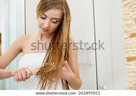 Hair. Beautiful Blond Brushing Her Wet Hair. Hair Care. Spa Beauty Model #262895051