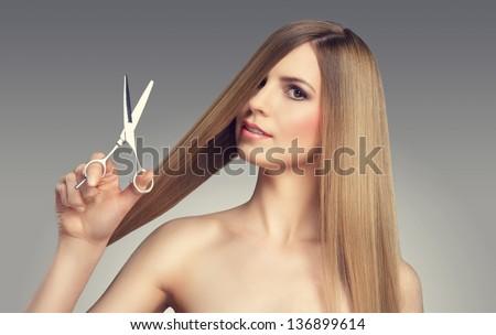Hair. Beautiful Blonde Girl. Healthy Long Hair. Beauty Model. Scissors