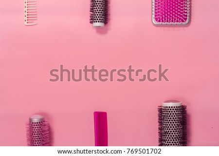 Hair brushes on the pink background. Top view