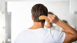 Hair Care. Close up rear view of young man hairbrushing with comb, looking in mirror