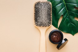 Hair care concept. Wooden hair comb and natural hair mask lie on beige background. Spa hair care.