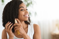 Hair Care. Happy Afro Woman Using Oil For Split Ends While Getting Ready At Home, Closeup Image With Copy Space