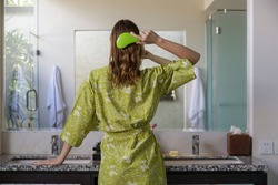 Hair care. Rare view of brunette woman combing hair with plastic detangling hair brush in the bathroom in front of the mirror.