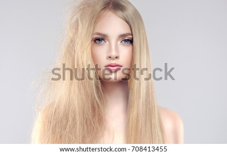 Hair care . Straightening ,smoothing and treatment of the hair .  Girl with straight and smooth hair on one side of the head . The second side of the head tangled and un brushed hair .