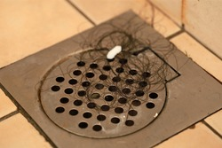 Hair clump in bath drain, dirty strongly stain on tile surface on the floor and walls shower room.
