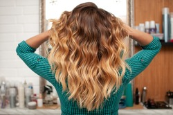 Hair coloring gradient from light golden to brown on a girl with long curly hair in the back
