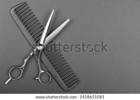 Hair cutting scissors and сomb, two pair texturizing or thinning shears for haircut, professional salon equipment. Copy space, flat lay