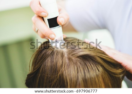 Hair doctor checking hair. Diagnostics hair and scalp.Trihoskopiya. Doctor examine patient female hair a special apparatus