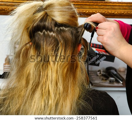 hair dresser hands make curls with curling tongs close up photo