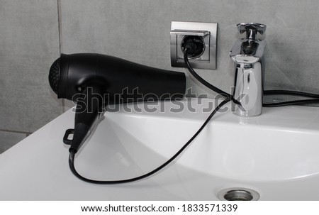 Hair dryer connected. A black hair dryer for drying hair lies in the bathroom on a white washbasin.