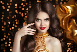 Hair. Makeup. Elegant brunette. Beautiful happy smiling woman portrait with red lips makeup and healthy long wavy hairstyle posing over golden star balloons, Christmas boker background.