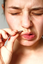 hair over the upper lip in women. girl with tweezers plucks a mustache. female antennae. problem skin