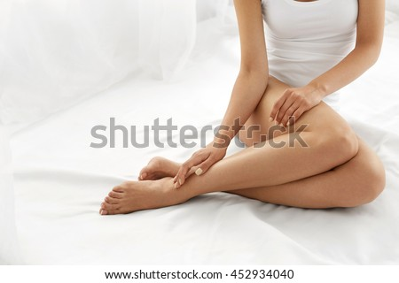 Hair Removal Concept. Closeup Of Beautiful Woman's Hand With Natural Manicure Touching Sexy Long Legs. Young Female Touching Her Perfect Hairless Smooth Soft And Silky Skin. Beauty Body Care Concept - Shutterstock ID 452934040
