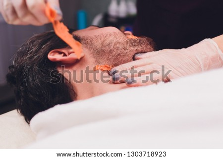 Hair removal. Man's face sugaring epilations beard trimming, yellow color, in cosmetology on the couch. #1303718923