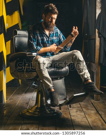 Hair style and hair stylist. Beard styling cut. Barber shop tools on old wooden background with copy space. Bearded man
