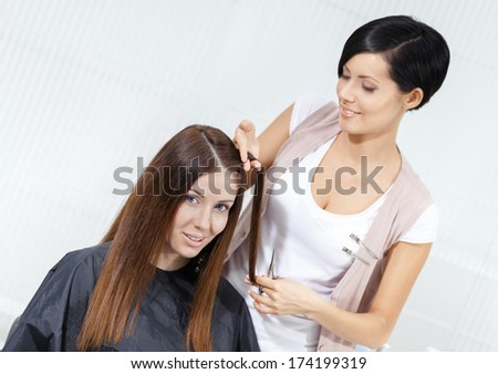 Hair stylist cuts hair of woman in hairdresser\'s. Concept of fashion and beauty