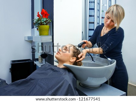 hair stylist washing woman hair in salon