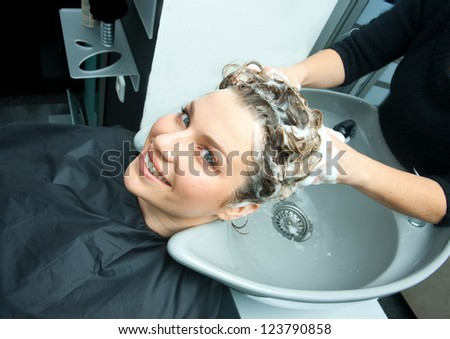 hair stylist washing woman hair in salon