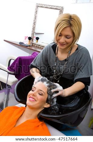 hair stylist washing woman head in hair salon