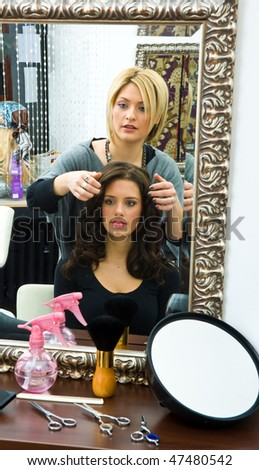 hair stylist work on happy woman hair in salon