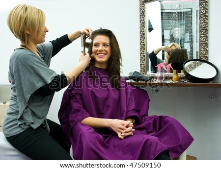 hair stylist work on happy woman hair in salon