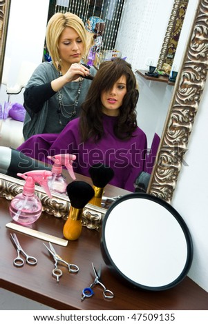 hair stylist work on woman hair in salon
