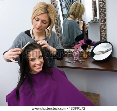 hair stylist work on woman hair in salon