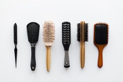 hair tools, beauty and hairdressing concept - different brushes or combs on white background