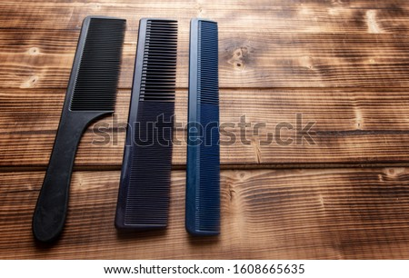 Hairbrushes for haircuts on a wooden background.