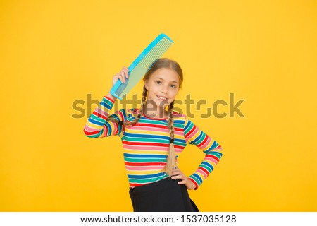 Haircare begins with combing. Little child hold hair comb yellow background. Haircare and combing. Haircare routine. Haircare to avoid clotted and tangle hair. Beauty hair salon.