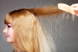 Haircare. Blonde woman with electrified long straight hair gray background