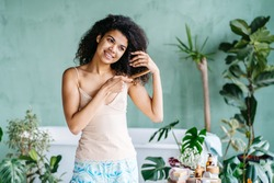 Haircare, morning routine, eco friendly zero waste concept. American multiethnic female combing brown thick curly hair with wooden comb on green natural bathroom interior with plants on background.