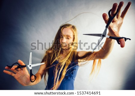 Haircut coiffure haircare concept. Crazy girl with blowing long blonde hair holding scissors, showing work tools normal and thinning shears