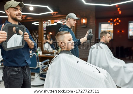 Haircut for little boy. Young smiling barber holding a mirror and showing the result of his work to cute little boy sitting in barber shop chair. Child visiting barber shop. Childrens hairdresser