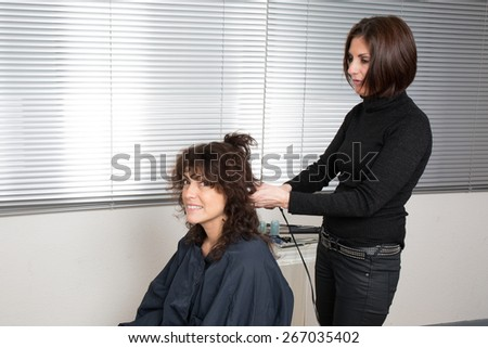 Hairdo with electric hair curler by a hair dresser