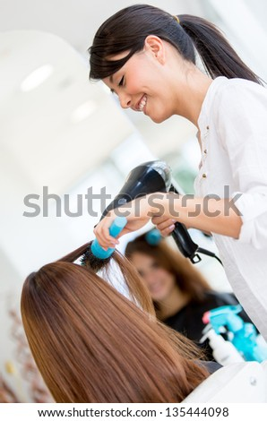 Hairdresser blowing woman\'s hair at the beauty salon