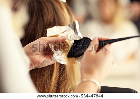 hairdresser coloring hair in studio