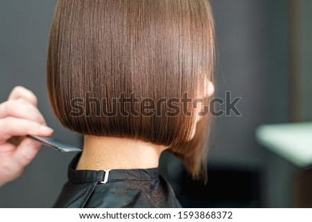 Hairdresser combs woman's brunette short hair with comb, close up, copy space.