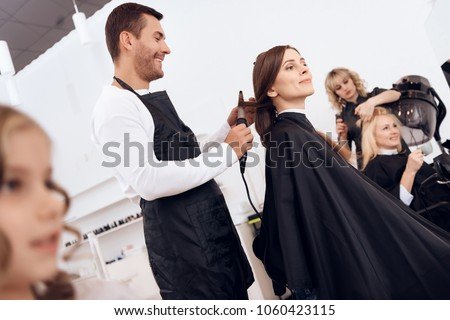 Hairdresser curling dark brown hair of beautiful woman. Woman care about hairstyle. Adult beautiful woman is doing hairdo in beauty salon.