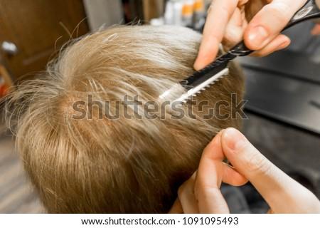 hairdresser cuts a man close up #1091095493