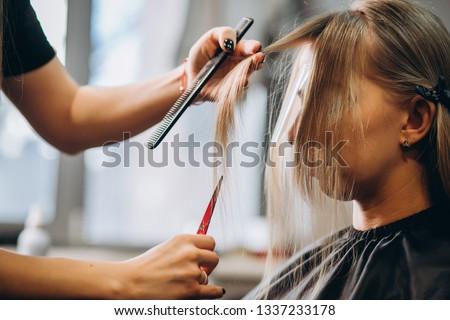 Hairdresser cuts hair by scissors beautiful blonde girl