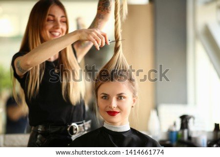 Hairdresser Cutting by Scissors Ponytail Portrait. Woman with Smile Getting Haircut in Beauty Salon. Female with Long Straight Hair Sitting in Studio with Funny Hairstyle Front View Shot. #1414661774