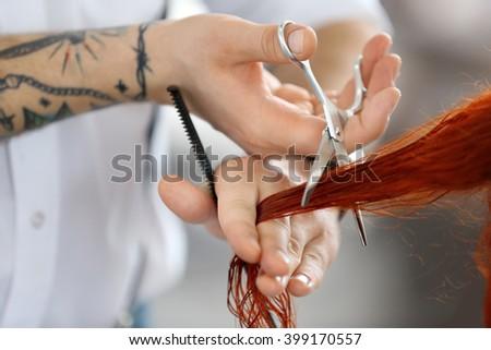 Hairdresser cutting red curls #399170557