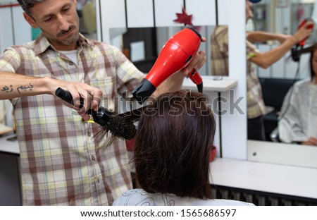 """Hairdresser drying hair and making a hairstyle, using hair brush and hair dryer,  to the young brunette woman at the hairdresser salon. Tattoo on hairdressers hand in arabic means """"I am not afraid""""."""